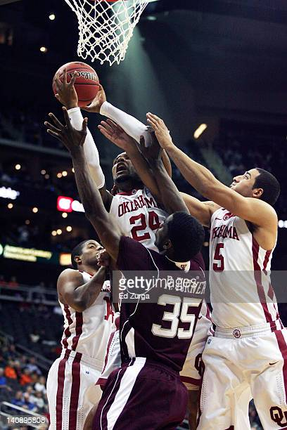 Romero Osby of the Oklahoma Sooners takes a shot over Ray Turner of Texas A&M during the first round of the Big 12 Basketball Tournament March 7,...
