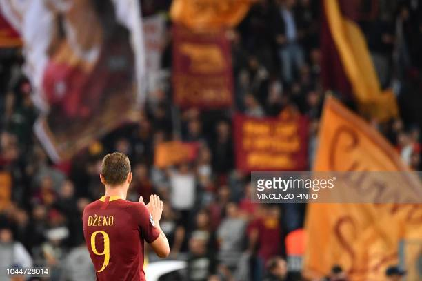 AS Rome's Bosnian forward Edin Dzeko acknowledges the public after scoring his third goal during the UEFA Champions League group G football match...