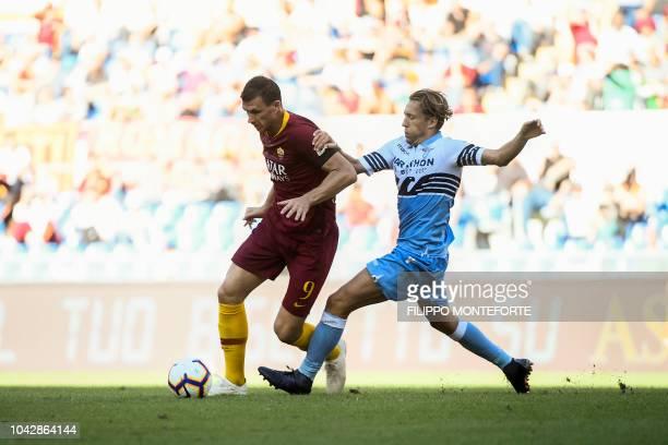 AS Rome's Bosnian forward Edin Dzeko outruns Lazio's Brazilian midfielder Lucas Leiva during the Italian Serie A football match AS Rome vs Lazio Rome...