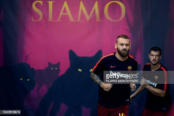AS Rome's Italian midfielder Daniele De Rossi enters the pitch for a warm up session prior to the Italian Serie A football match AS Rome vs Lazio...