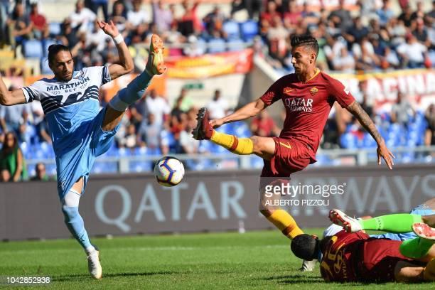 AS Rome's Italian midfielder Lorenzo Pellegrini and Lazio's Uruguayan defender Martin Caceres go for the ball before Pellegrini opens the scoring...