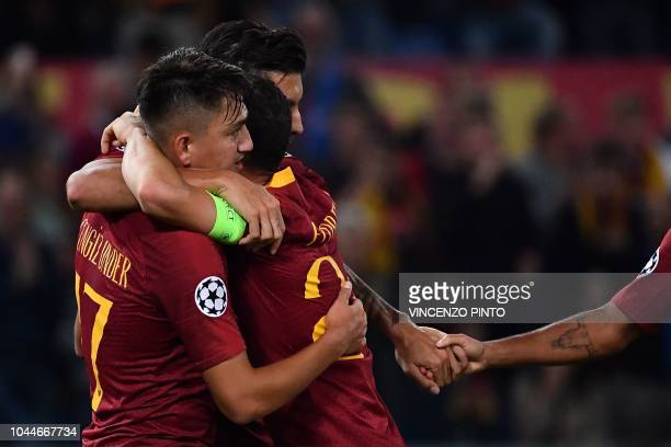 Rome's Turkish forward Cengiz Under celebrates with teammates after scoring during the UEFA Champions League group G football match between AS Roma...