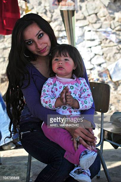 Romina Gomez daughter of Mario Gomez one of the 33 miners trapped in San Jose mine poses with her daughter Camila Campiyai at the encampment near...