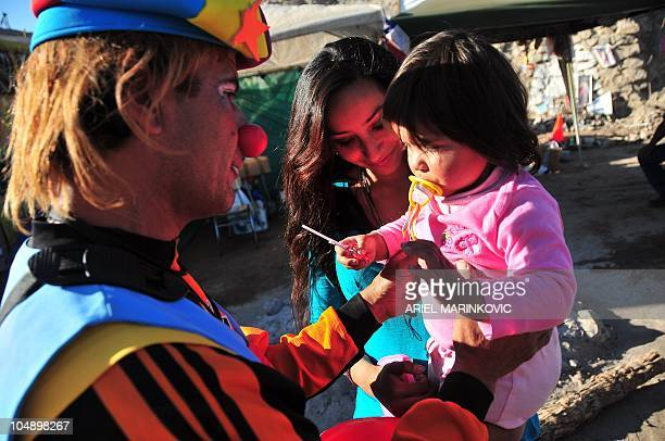 Romina Gomez daughter of Mario Gomez one of the 33 miners trapped in the shafts plays with her daughter Camila Campillay and a clown at La Esperanza...