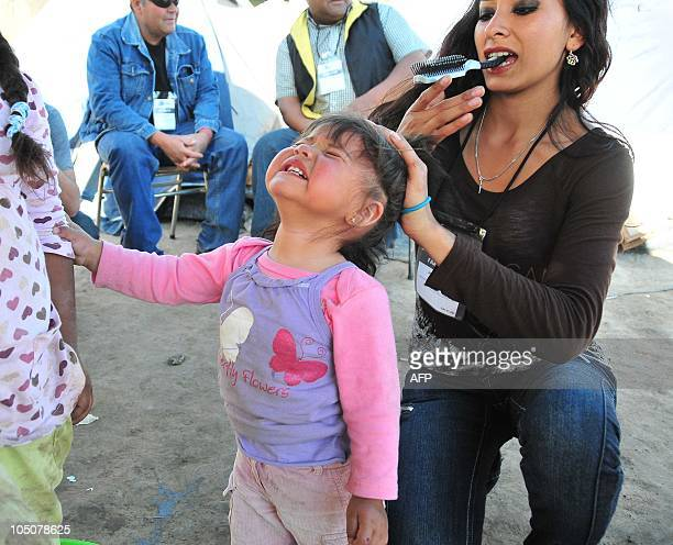 Romina Gomez daughter of trapped miner Mario Gomez combs the hair of her daughter Camila at La Esperanza encampment near Copiapo Chile October 8 2010...