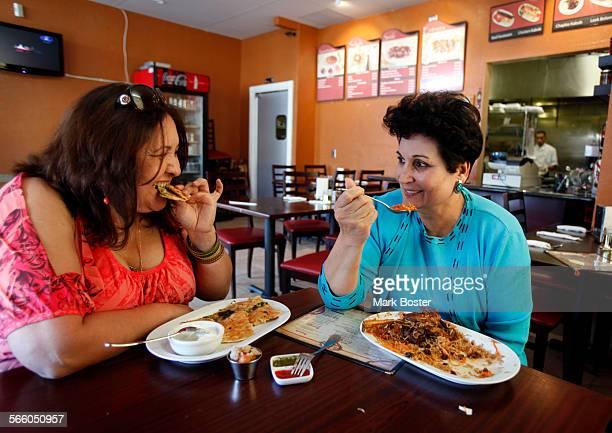 Romina Naiam eats a dessert of Sheer Birinj while Razia Amiry tries the Quabuli Pallow at Chili Chutney in Lake Forest January 14 2011 The restaurant...