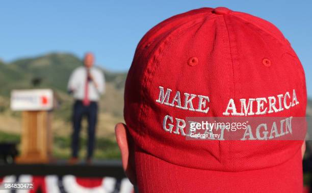 Romney supporter listens to a speaker as he wears a Make America Great Again hat at the Mitt Romney election party on June 26 2018 in Orem Utah It is...