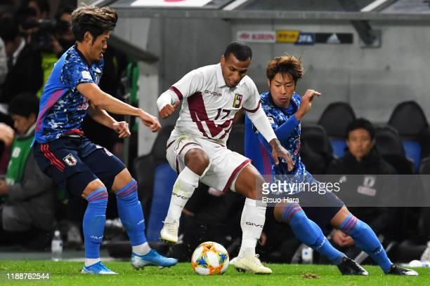 Romulo Otero of Venezuela controls the ball under pressure from Hotaru Yamaguchi and Genta Miura of Japan during the international friendly match...