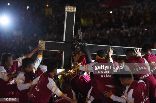 Romy Roxas one of the guards supervises the statue of the Black Nazarene being placed in the carriage at the start of the annual religious procession...