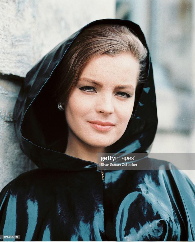 Romy Schneider (1938-1982), Austrian actress, wearing a dark plastic raincoat, with the hood up, circa 1970.