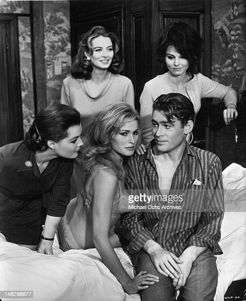 Romy Schneider Capucine Ursula Andress Peter O'Toole and Paula Prentiss gathered around bed in a scene from the film 'What's New Pussycat' 1965