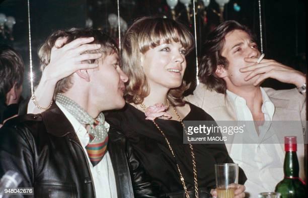Romy Schneider entourée de Helmut Berger et Daniel Biaisini au cabaret 'L'Ange Bleu' le 4 mai 1975 à Paris France