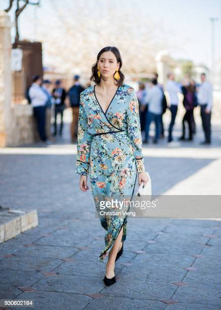 Romy Spector wearing dress with floral print and slit white bag is seen during Tel Aviv Fashion Week on March 11 2018 in Tel Aviv Israel
