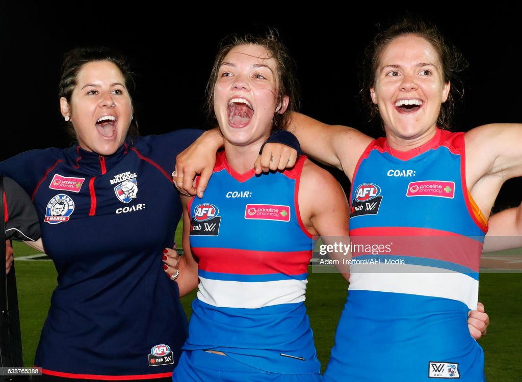 Romy Timmins, Ellie Blackburn and Emma Kearney of the Bulldogs sing the team song during the 2017 AFLW Round 01 match between the Western Bulldogs and the Fremantle Dockers at VU Whitten Oval on February 4, 2017 in Melbourne, Australia.