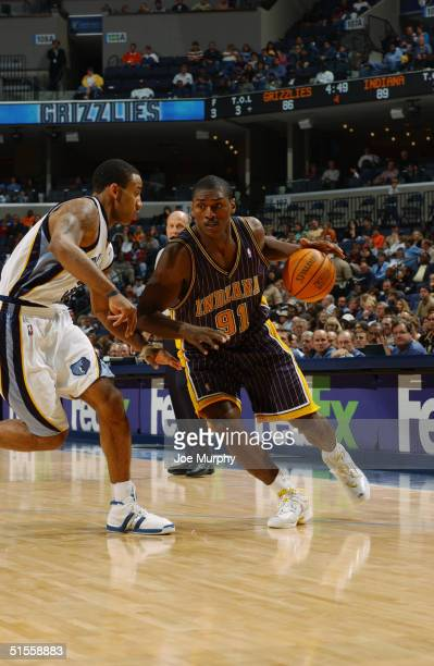 Ron Artest of the Indiana Pacers drives around Dahntay Jones of the Memphis Grizzlies during the game at FedEx Forum on October 16 2004 in Memphis...