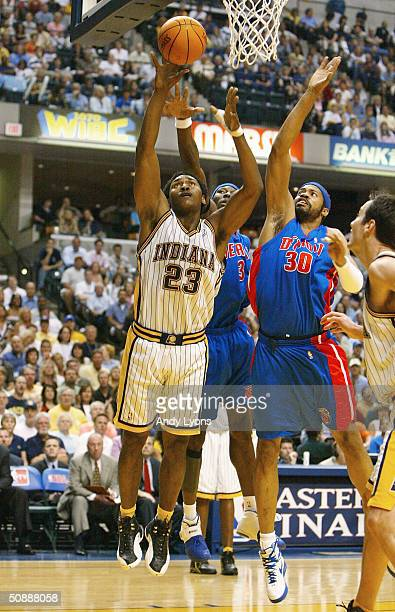 Ron Artest of the Indiana Pacers goes to the basket past Ben Wallace and Rasheed Wallace of the Detroit Pistons in Game one of the Eastern Conference...
