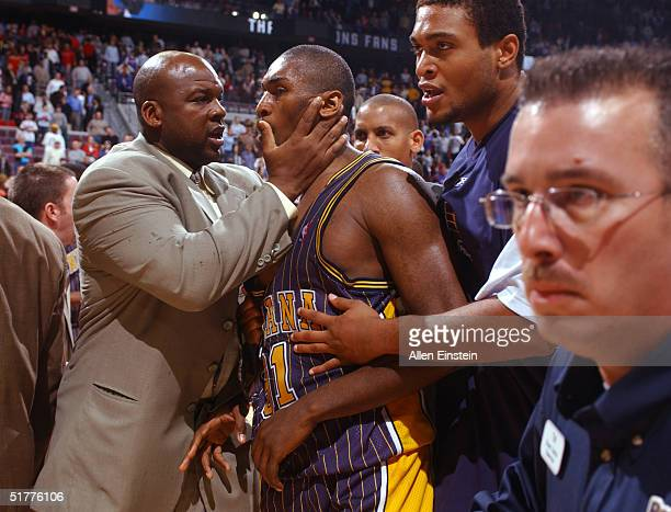 Ron Artest of the Indiana Pacers is restrained during a melee involving fans during a game against the Detroit Pistons November 19 2004 at the Palace...