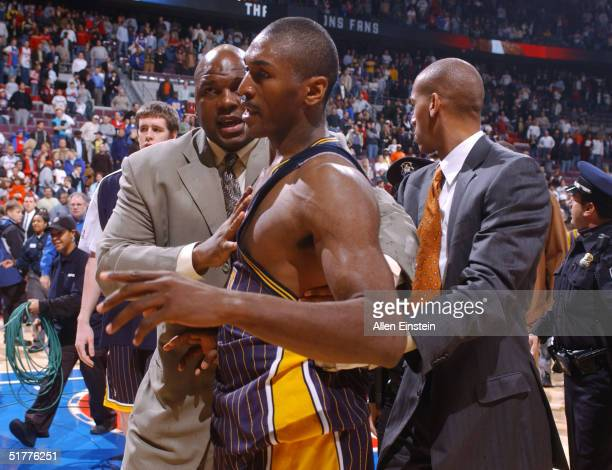 Ron Artest of the Indiana Pacers is restrained during a melee involving fans during a game against the Detroit Pistons November 19, 2004 at the...