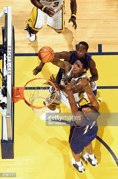 Ron Artest of the Indiana Pacers splits Jarvis Hayes and Brevin Knight of the Washington Wizards on December 9 2003 at Conseco Fieldhouse in...
