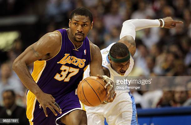 Ron Artest of the Los Angeles Lakers collects a loose ball and dribbles away from Carmelo Anthony of the Denver Nuggets during NBA action at the...