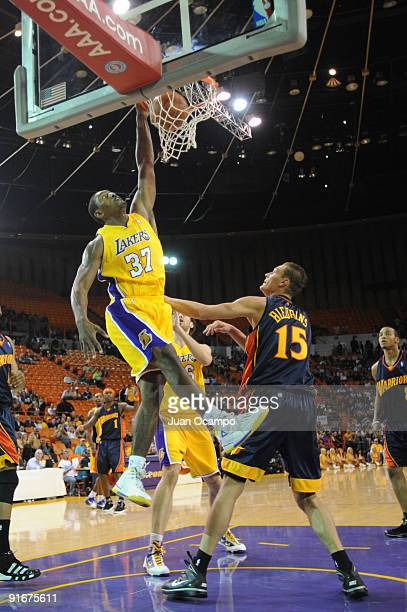 Ron Artest of the Los Angeles Lakers dunks against Andris Biedrins of the Golden State Warriors during a pre-season game at The Forum on October 9,...