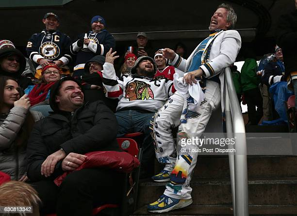 Ron Baechle better known to St Louis Blues fans as The Towel Man enjoys a Blues score at the expense of Chicago Blackhawks fan Chris Reyes of Crown...