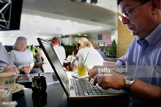 – – Ron Bain answers email from his laptop while waiting for flight to Sydney Australia at bar in Tom Bradley terminal at LAX Bain is returning home...