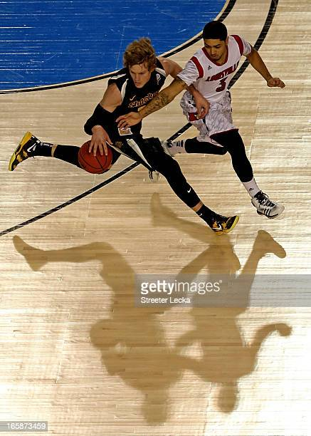 Ron Baker of the Wichita State Shockers brings the ball up court in the second half against Peyton Siva of the Louisville Cardinals during the 2013...
