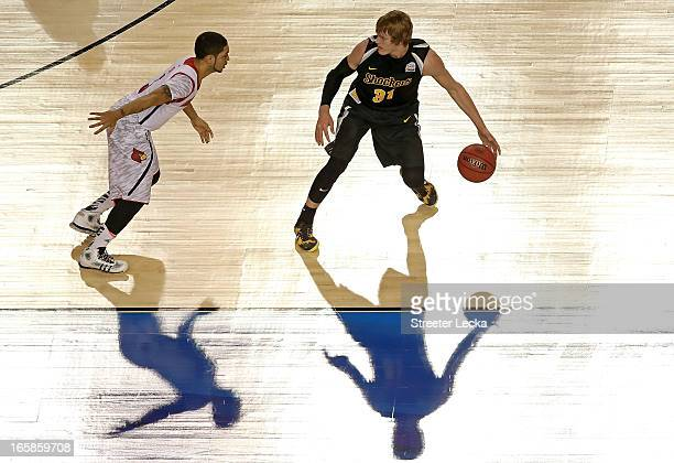 Ron Baker of the Wichita State Shockers runs the offense in the first half against Peyton Siva of the Louisville Cardinals during the 2013 NCAA Men's...