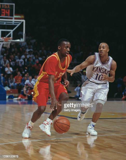 Ron Bayless, Guard for the Iowa State Cyclones dribbles the ball down court past Calvin Rayford of the University of Kansas Jayhawks during the NCAA...
