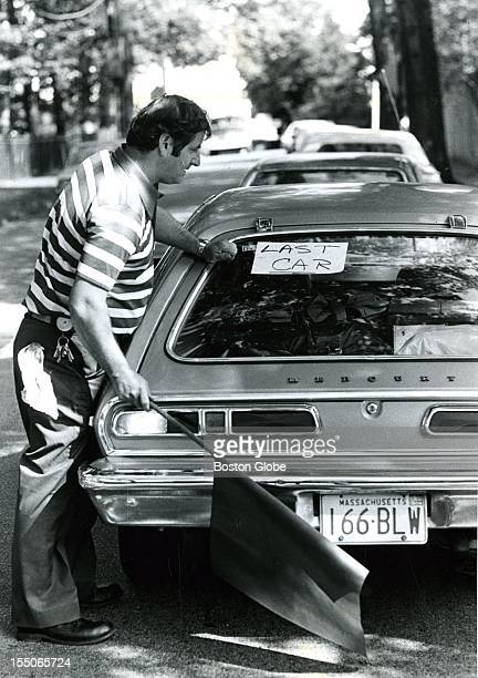 "Ron Clancy carries a red flag and posts a ""last car"" sign on the car at the end of line, waiting to fill up at Texico in Chestnut Hill during a gas..."