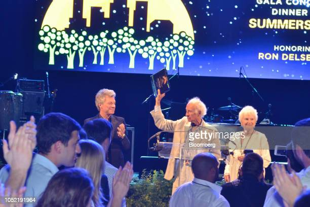 Ron Delsener center accepts an award on stage with Jon Bon Jovi and Nancy Hoving during the City Parks Foundation Gala event in New York US on Monday...