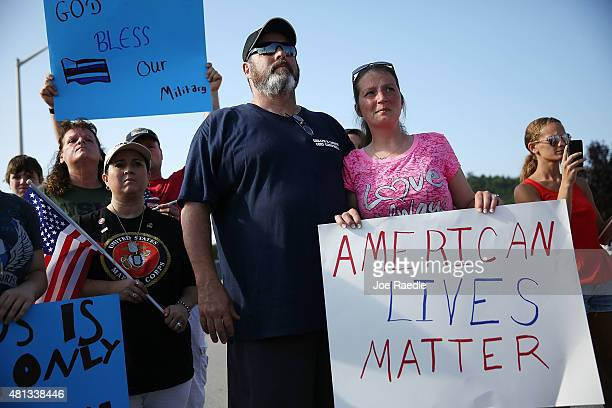 Ron Fahy and Misty Fahy hold a sign that reads' American Lives Matter' as they attend a prayer service near the Armed Forces Career Center/National...