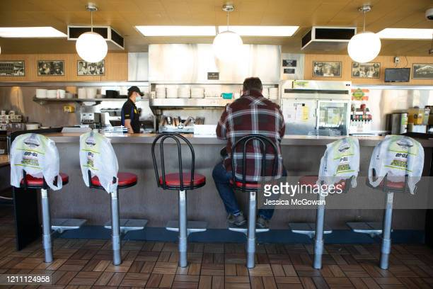 Ron Flexon sits at the counter for dine-in service while other seats are marked off for social distancing protocol at the Waffle House on April 27,...