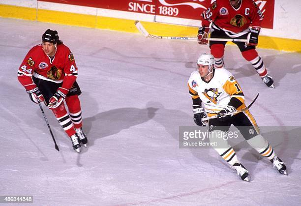 Ron Francis of the Pittsburgh Penguins and Mike Peluso of the Chicago Blackhawks follow the play during Game 1 of the 1992 Stanley Cup Finals on May...