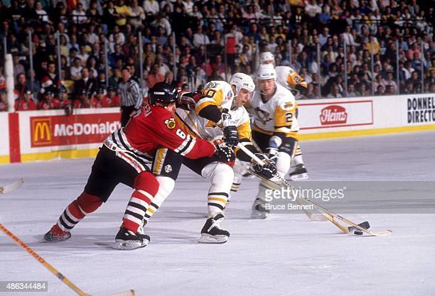 Ron Francis of the Pittsburgh Penguins controls the puck as Frantisek Kucera of the Chicago Blackhawks goes for the poke check during Game 1 of the...