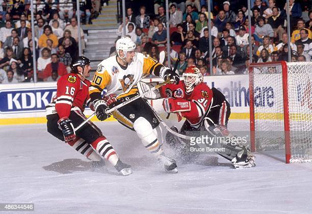 Ron Francis of the Pittsburgh Penguins crashes into goalie Ed Belfour of the Chicago Blackhawks as Michel Goulet of the Blackhawks follows behind...