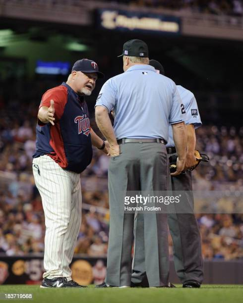 Ron Gardenhire of the Minnesota Twins speaks with umpires Dale Scott and Bill Miller during the game against the Oakland Athletics on September 11...