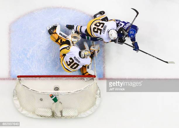 Ron Hainsey and Matt Murray of the Pittsburgh Penguins look on as Michael Chaput of the Vancouver Canucks scores during their NHL game at Rogers...