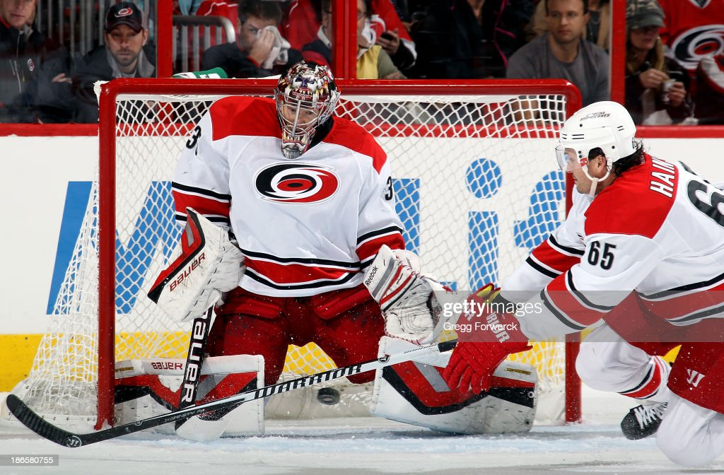 Ron Hainsey #65 of the Carolina Hurricanes lunges toward a Tampa Bay Lightning shot that would be smothered by teammate Justin Peters #35 during the first period of an NHL game at PNC Arena on November1, 2013 in Raleigh, North Carolina.