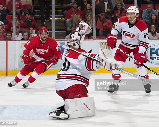 Ron Hainsey of the Carolina Hurricanes watches teammate Cam Ward make a stretching glove save with Frans Nielsen of the Detroit Red Wings to the side...