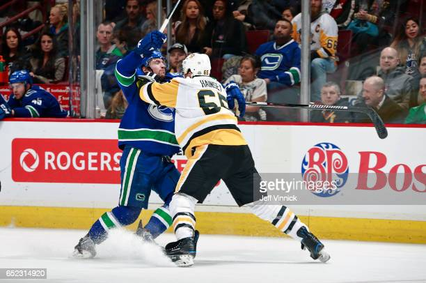 Ron Hainsey of the Pittsburgh Penguins checks Sven Baertschi of the Vancouver Canucks during their NHL game at Rogers Arena March 11, 2017 in...