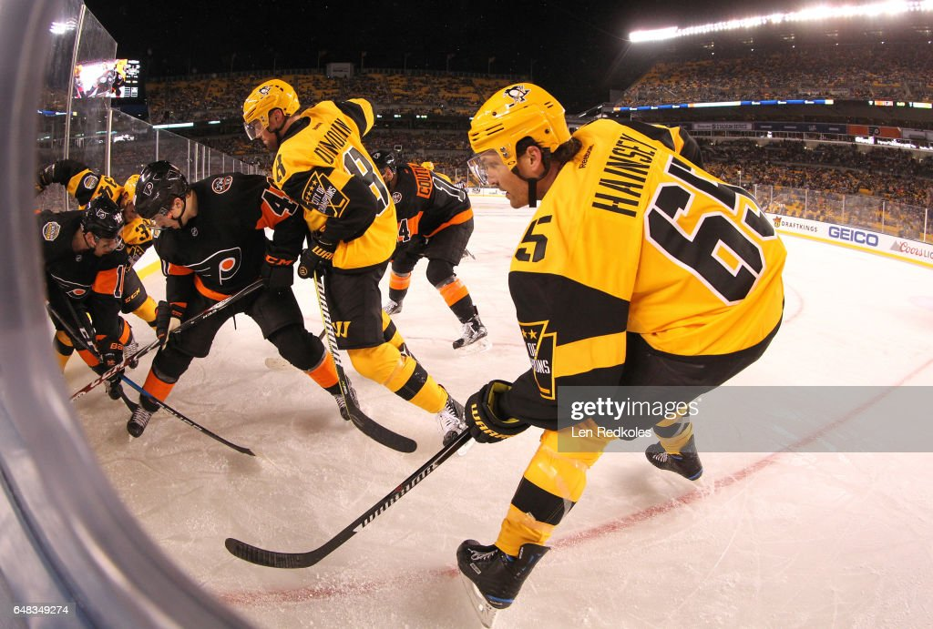 Ron Hainsey #65 of the Pittsburgh Penguins supports teammate Brian Dumoulin #8 in the corner during the third period of the 2017 Coors Light NHL Stadium Series game at Heinz Field on February 25, 2017 in Pittsburgh, Pennsylvania.
