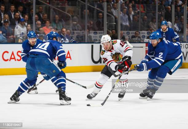 Ron Hainsey of the Toronto Maple Leafs and Morgan Rielly defend against Alex DeBrincat of the Chicago Blackhawks during the first period at the...