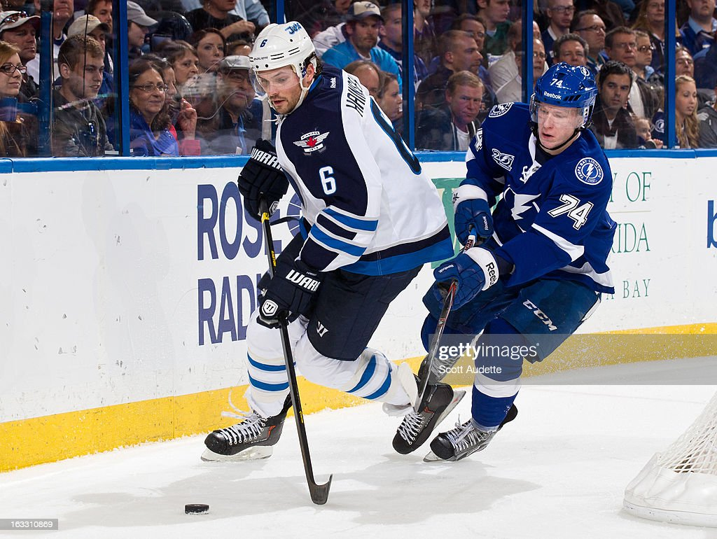 Ron Hainsey #6 of the Winnipeg Jets controls the puck in front of Ondrej Palat #74 of the Tampa Bay Lightning during the third period of the game at the Tampa Bay Times Forum on March 7, 2013 in Tampa, Florida.
