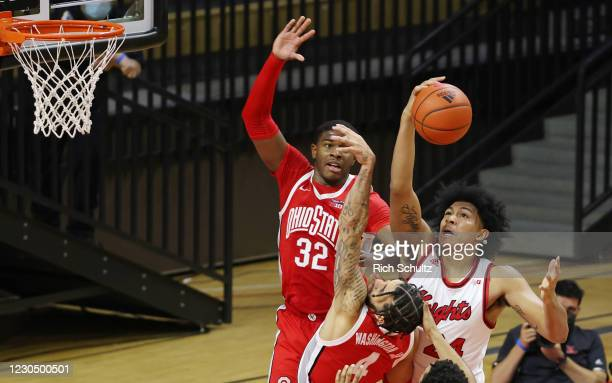 Ron Harper Jr. #24 of the Rutgers Scarlet Knights pulls a rebound away from E.J. Liddell and Duane Washington Jr. #4 during the first half of a...