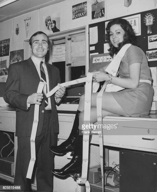 Ron Harris Captain of Chelsea F C passes computerised tickets from the new Ticketron terminal to Chelsea fan Jackie Butterworth at Stamford Bridge...