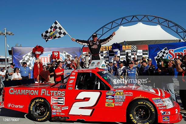 Ron Hornaday driver of the Champion Chevrolet celebrates in victory lane after winning the NASCAR Camping World Truck Series Smith's 350 on October...