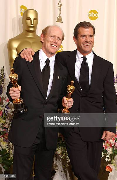 Ron Howard winner in the Best Director and Best Picture categories for A Beautiful Mind poses with presenter Mel Gibson for photographers backstage...