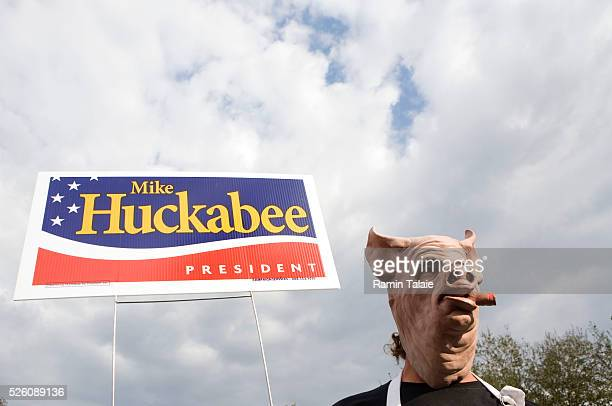 Ron Mattson wears a pig mask and stands near a campaign sign for Republican presidential hopeful Mike Huckabee at a pig fair in Lakeland, Florida.